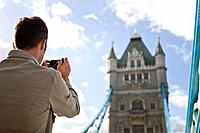 A mid_adult man taking a photograph of Tower Bridge