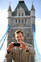 A mid_adult man taking a photograph of himself in front of Tower Bridge
