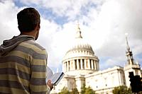 A mid_adult man standing in front of St Paul's cathedral, looking at a guidebook