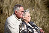 A senior couple sitting amongst the sand dunes, embracing