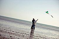 A senior couple flying a kite on the beach
