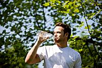 A young man drinking a bottle of water, outdoors