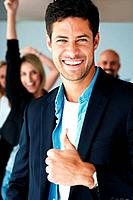 Portrait of smiling business man showing a thumbs up with excited colleagues at the back