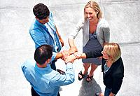 Top view of small group of business people joining hands and smiling