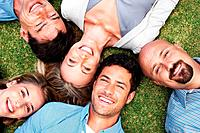 Portrait of a group of people together lying on grass with a smile