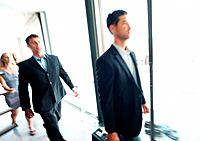 Blurred image of a group of business people walking in office