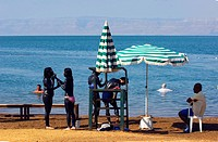 four teenage tourists putting black medical mud onto their whole bodies at a beach at the Dead Sea, Jordan
