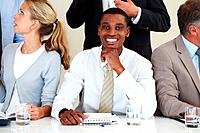 Confident young afroamerican businessman smiling at a meeting with associates
