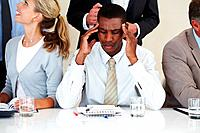 Young afroamerican businessman suffering from headache during a meeting at office
