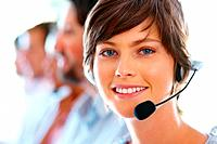 Smiling call center executive with colleagues in blur background