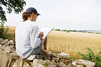 Woman sitting on wall and sketching