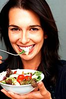 Pretty woman smiling while ready to eat salad