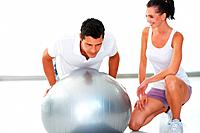 Trainer working on exercise ball while woman looking at him