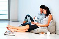 Relaxed young couple using laptop at home