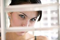 Young Woman Behind Venetian Blind