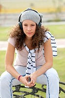Cute young woman listening music with headphones