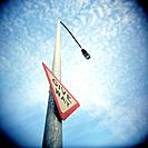 Give Way Sign on Streetlight Against Sky