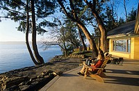Couple sitting on deck of rammed earth house, Salt Spring Island, British Columbia, Canada