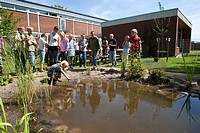 primary school pupils catching animals in the self_built pond in the school garden