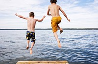two boys 9 &amp; 12 years old jumping off dock into lake, Sylvan Lake, Alberta, Canada