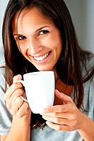 Pretty woman smiling while holding coffee cup