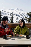 Couple enjoying lunch at a chalet, Whistler, British Columbia, Canada.