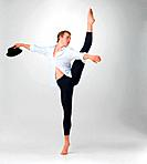 Full length of a male ballet dancer performing a step with hat in hand against white _ copyspace