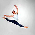 Full length of a young ballet dancer practicing high jump against white background _ copyspace