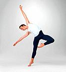 Full length of a male ballet dancer performing a balancing act against white background