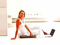 Side view of a relaxed casual mature woman sitting on floor and using laptop