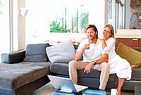 Portrait of a happy relaxed mature couple sitting together on couch at home