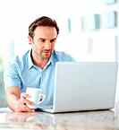 Portrait of a happy young male holding cup of coffee and using a laptop _ Indoor