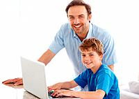 Portrait of a handsome young man and his son looking at you while working on laptop _ Indoor