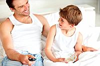 Portrait of little boy eating his breakfast with his father holding a tv remote control on bed