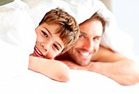 Portrait of a happy small boy lying on bed with his father under bedsheet