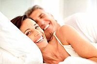 Portrait of happy mature couple lying in bed and smiling