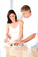 Portrait of beautiful mature woman cutting fresh fruit with her husband helping her