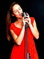 Portrait of a happy young female jazz singer singing with old fashioned microphone