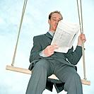 Businessman sitting on a swing reading newspaper