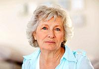 Closeup portrait of a sad senior woman against blurred background