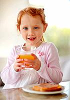 Portrait of a happy adorable little girl holding a glass of juice while having breakfast