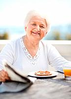 Portrait of a happy mature woman with newspaper and having her breakfast