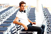 Portrait of young man sitting alone in auditorium with a laptop and headphone