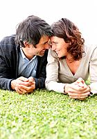 Portrait of a romantic mature couple lying together on a grassy lawn