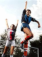 Two Cheering Teenage Girls Jumping in Front of Goal