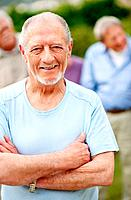 Portrait of retired old man smiling outdoors with people in background