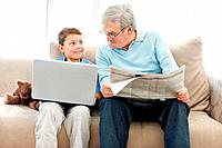 Elderly man sitting with a newspaper while a smiling little boy using a laptop _ Indoor