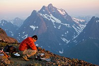 A lone climber prepares dinner while setting up camp on Elkhorn Mountain. Strathcona Park, Central Vancouver Island, British Columbia, Canada
