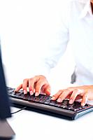Closeup of womans hands typing on computer keyboard
