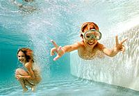 Girl and Boy Underwater in Swimming Pool